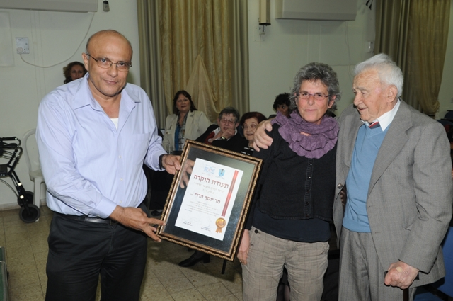 Mr. Eitan Cohen, administrative director, grants a Certificate of Recognition to the daughter of the first administrator, the late Mr. Joseph Hardy