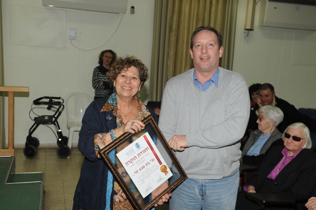 Yael Arbeli, the district nurse supervisor, offering a recognition certificate to the son of the first superintendent nurse, Mrs. Batsheva Levy